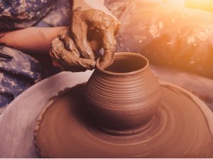 woman-hands-working-on-pottery-wheel-and-making-a-pot